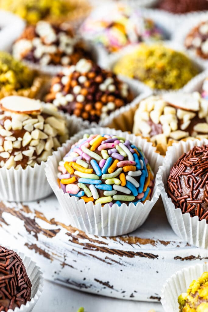 brigadeiros coated in sprinkles, chopped pistachios, chopped almonds.