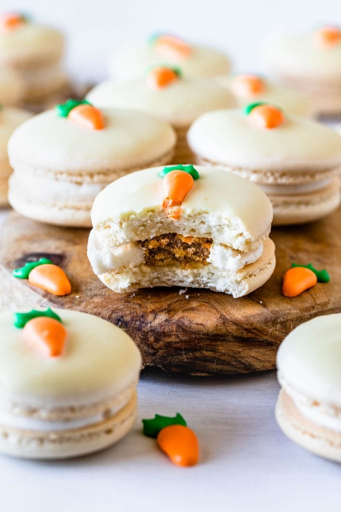 Carrot Cake Easter Macarons filled with carrot cake and cream cheese frosting topped with a royal icing carrot