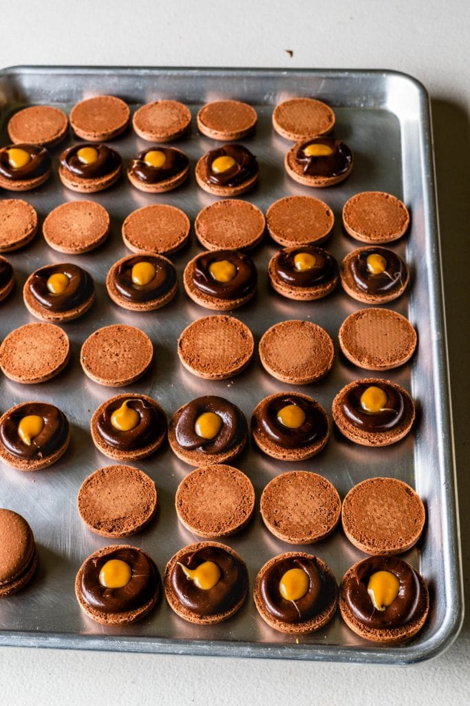 chocolate macaron shells filled with a ring of chocolate ganache, and caramel filling in the middle