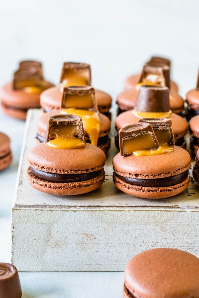Chocolate Caramel Macaron in the front filled with caramel and chocolate topped with a rolo candy on top of a white box