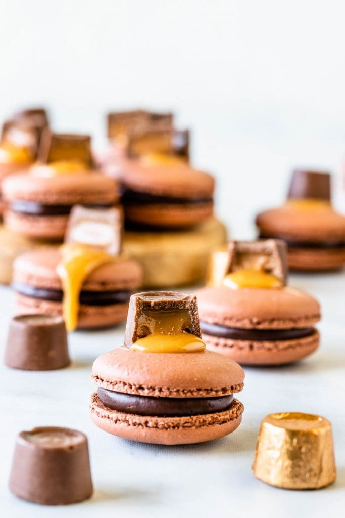 Chocolate Caramel Macaron in the front filled with caramel and chocolate topped with a rolo candy and caramel sauce