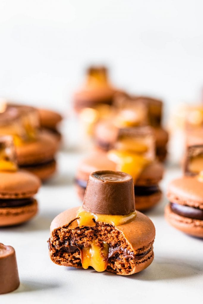 bitten Chocolate Caramel Macaron in the front filled with caramel and chocolate topped with a rolo candy with more macarons around it