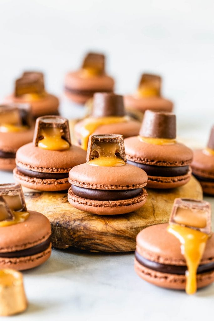 Chocolate Caramel Macaron in the front filled with caramel and chocolate topped with a rolo candy on a wooden board, with more macarons around it