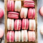 Pink, white, and dark pink strawberry rhubarb macarons in a box, from a bird's eye view, with jam in the top right corner
