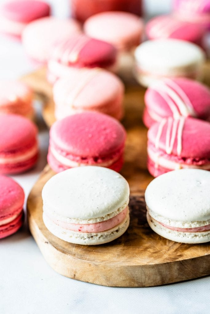 Pink, white, and dark pink strawberry rhubarb macarons on top of wooden board
