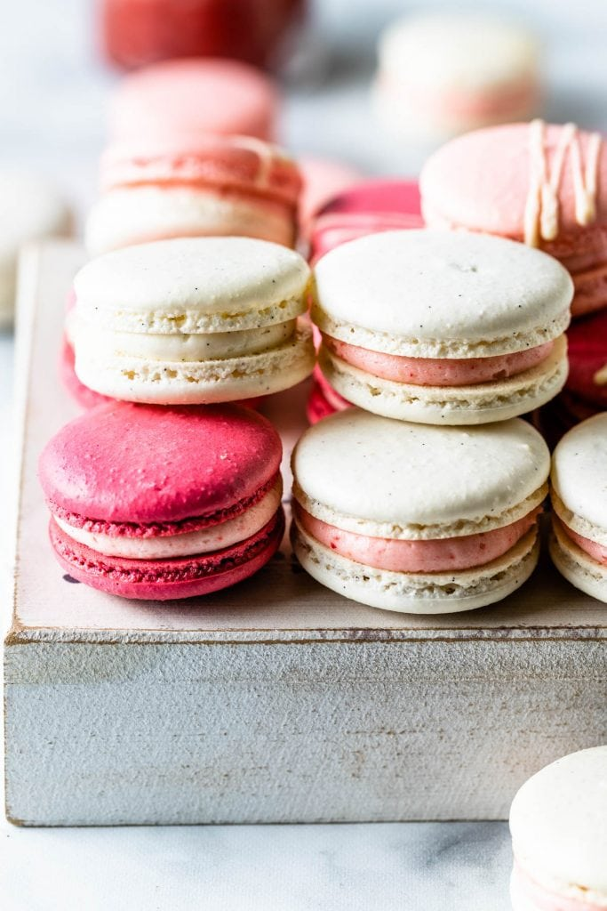 Pink, white, and dark pink strawberry rhubarb macarons on top of a white box