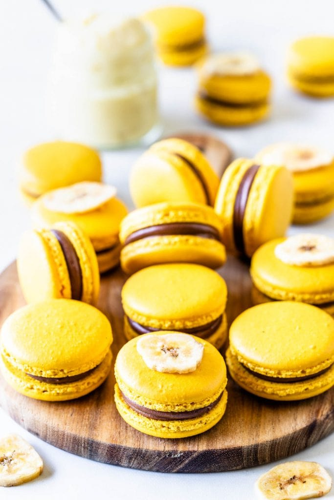 Banana Macarons yellow macarons in a box with chocolate and banana pudding filling on top of a wooden board