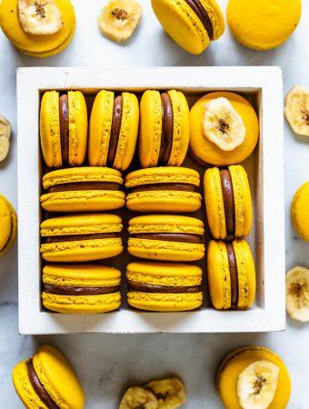 Banana Macarons yellow macarons in a box with chocolate and banana pudding filling, bird's eye view