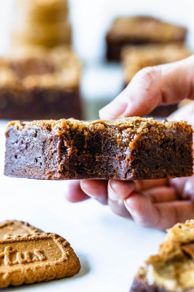 hand holding a slice of bitten biscoff brownie
