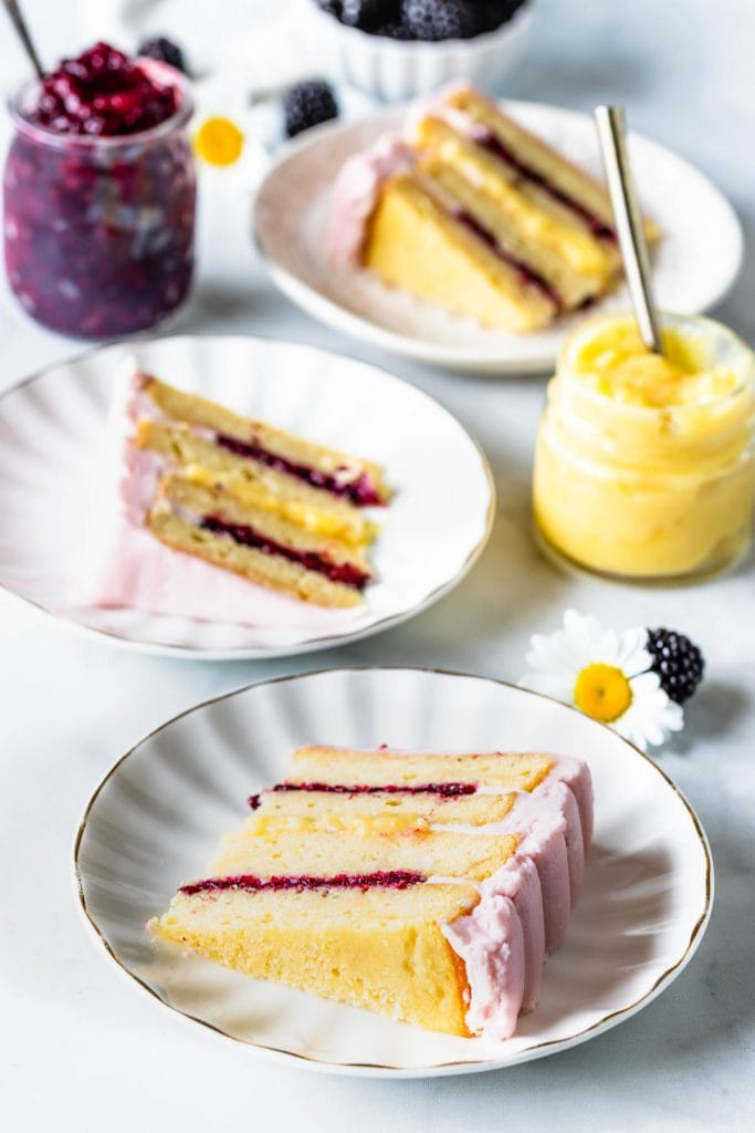 three slices of cake Lemon Blackberry Cake slice showing the top and bottom filling of blackberry jam, and the middle filling is lemon curd, covered in a pink blackberry buttercream