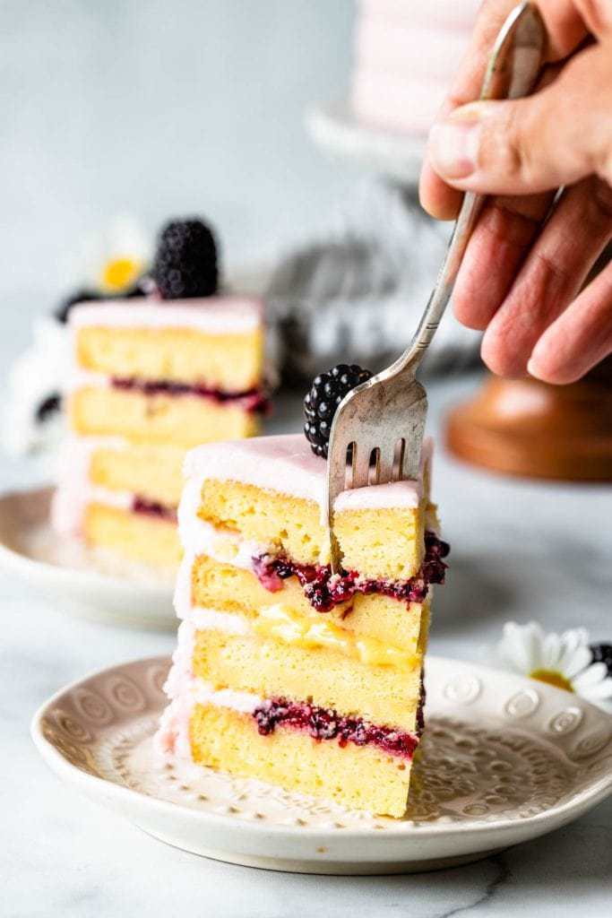 fork cutting through a slice of Lemon Blackberry Cake, showing the top and bottom filling of blackberry jam, and the middle filling is lemon curd, covered in a pink blackberry buttercream