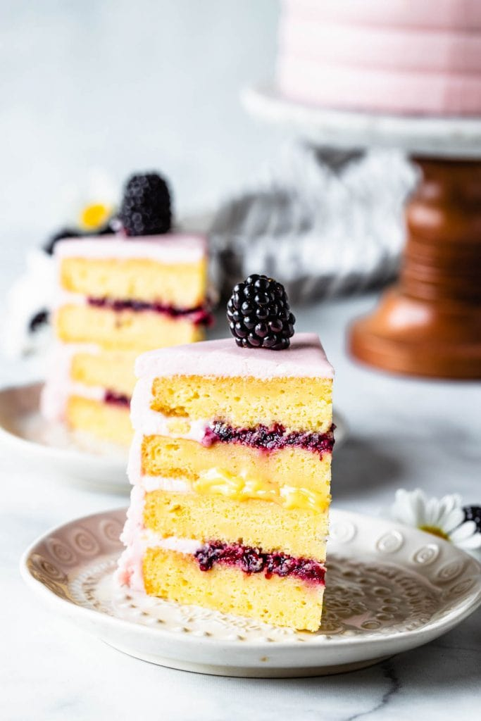 Lemon Blackberry Cake slice showing the top and bottom filling of blackberry jam, and the middle filling is lemon curd, covered in a pink blackberry buttercream
