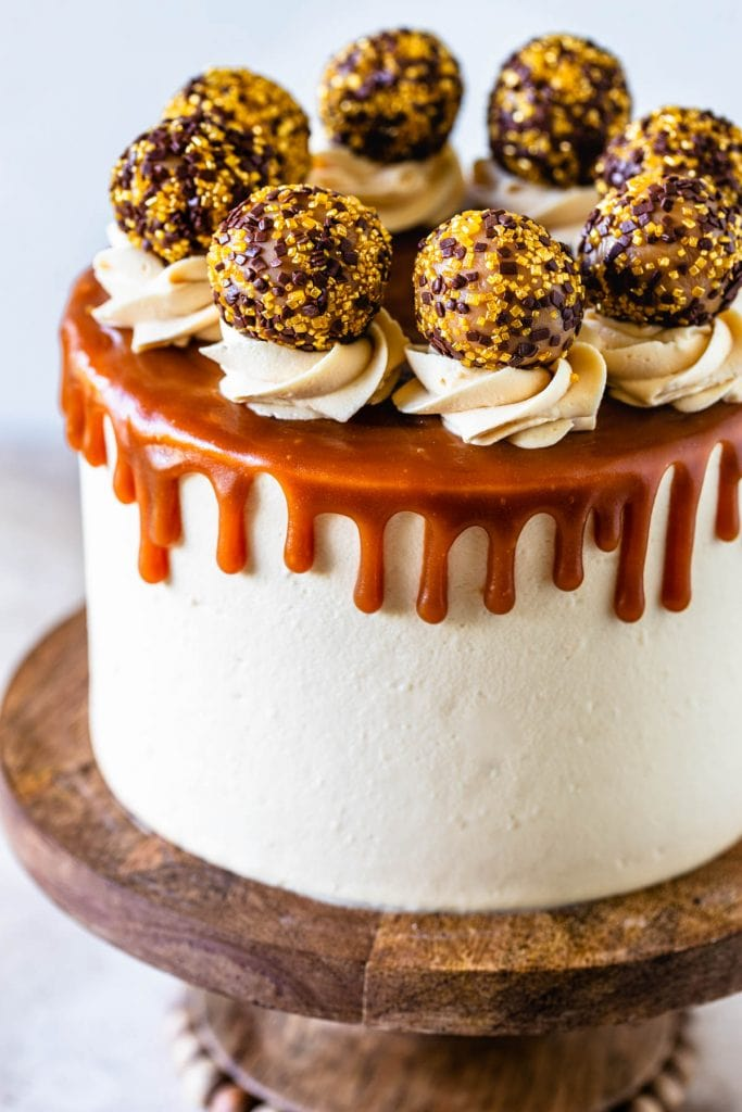 Caramel Chocolate Cake covered with caramel drip and caramel truffles on a wooden cake stand