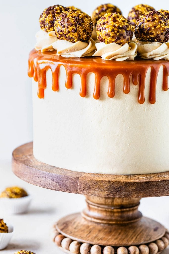 Salted Caramel Chocolate Cake covered with caramel drip and caramel truffles on a wooden cake stand