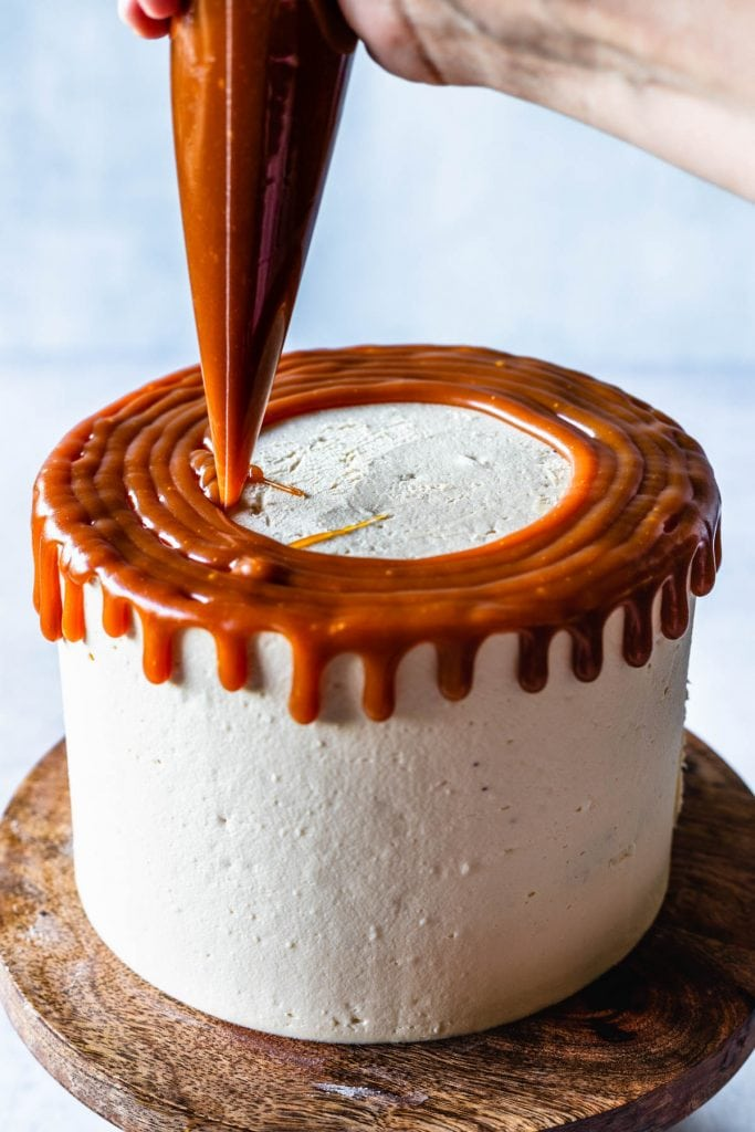 applying caramel drip to a cake, with a piping bag