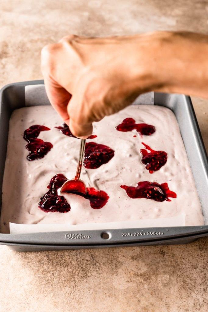 swirling raspberry jam in no-churn ice cream