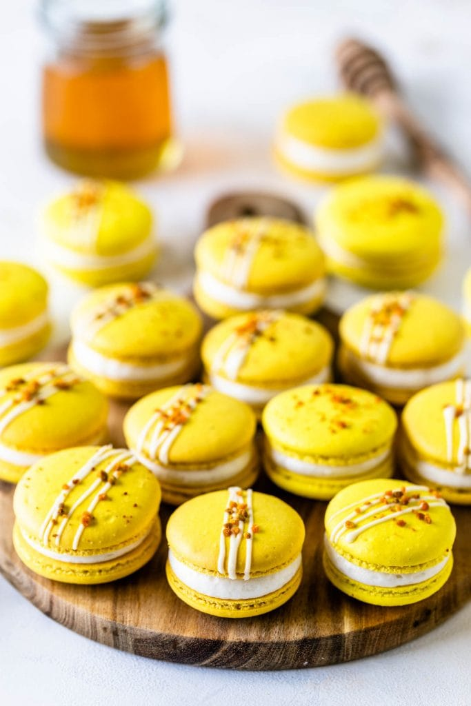 Honey Macarons topped with bee pollen on a wooden board with a jar of honey on the back