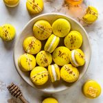 Honey Macarons topped with bee pollen in a plate, seeing from the top, with a jar of honey on the side, and a honey spoon