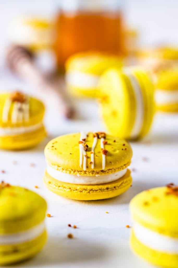 Honey Macarons topped with bee pollen with a jar of honey on the back