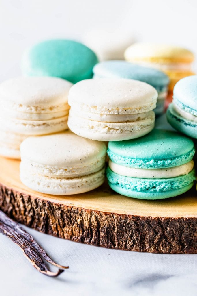 white, blue, teal, pink and yellow macarons on top of a wooden board