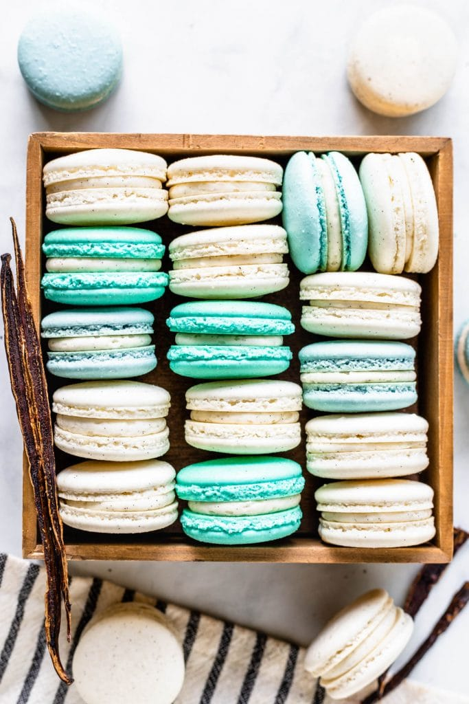 Vanilla Bean Macarons, green, white, blue, in a box, viewed from the top, with a vanilla pod on the side