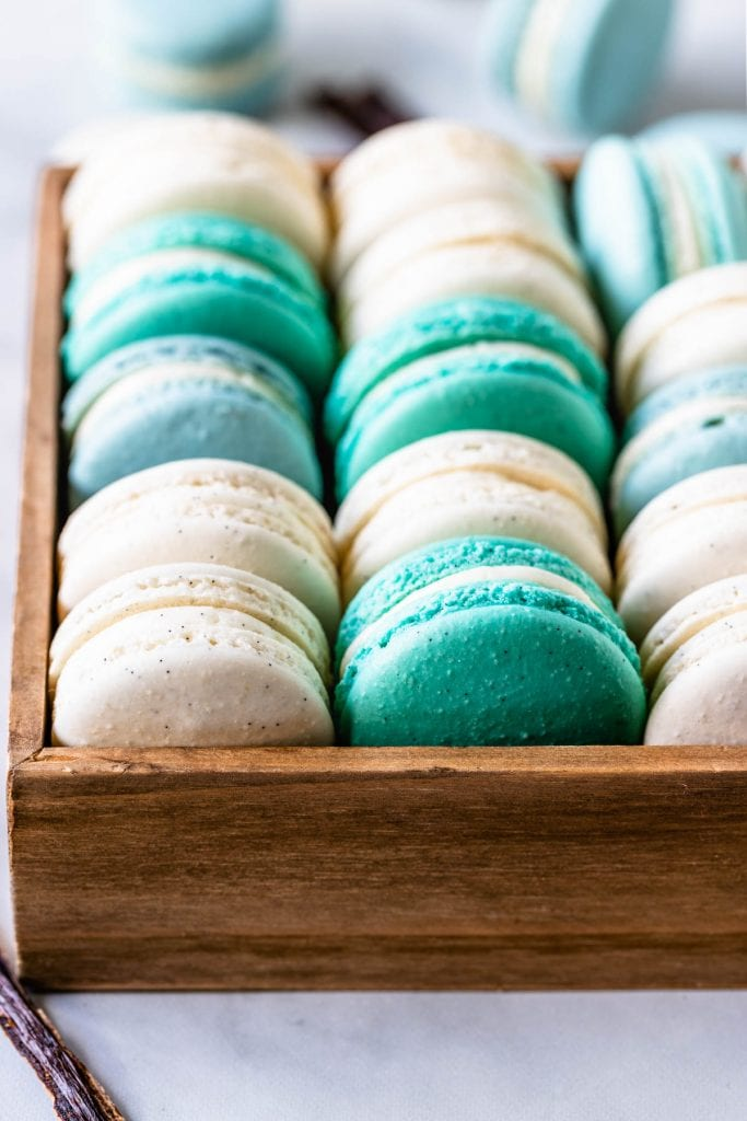 Vanilla Bean Macarons, green, white, blue, in a box, with a vanilla pod on the side