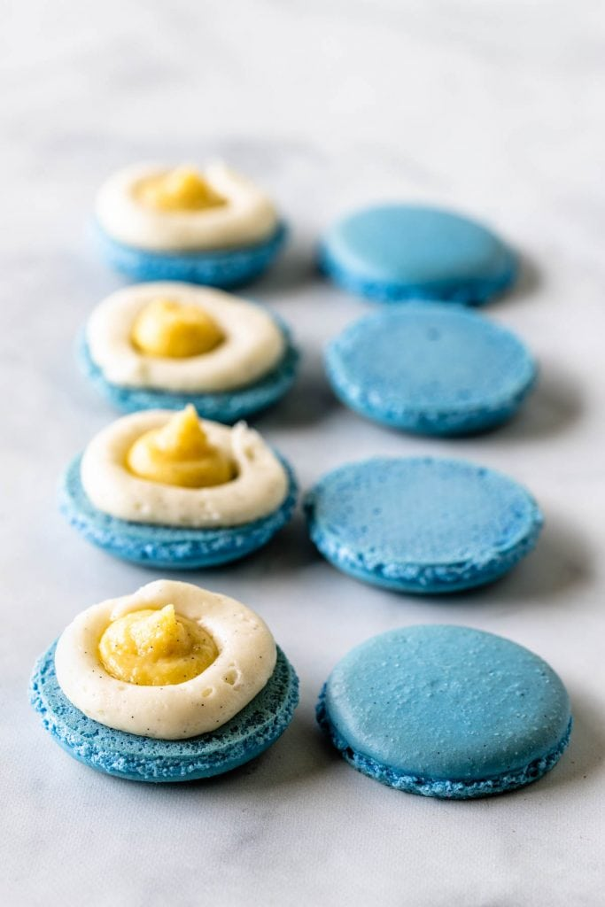 blue macaron shells filled with vanilla bean pastry cream and vanilla bean buttercream
