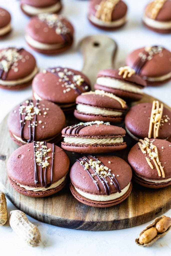 Peanut Butter Macarons topped with peanut butter drizzle and chopped peanuts on a wooden board