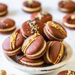 chocolate macarons with peanut butter filling in a bowl, with drizzled peanut butter and chocolate on top