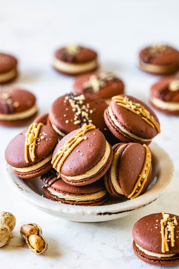 Peanut Butter Macarons topped with peanut butter drizzle and chopped peanuts in a bowl