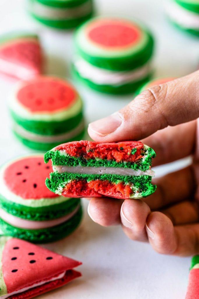 watermelon macaron cut in half showing the ganache filling