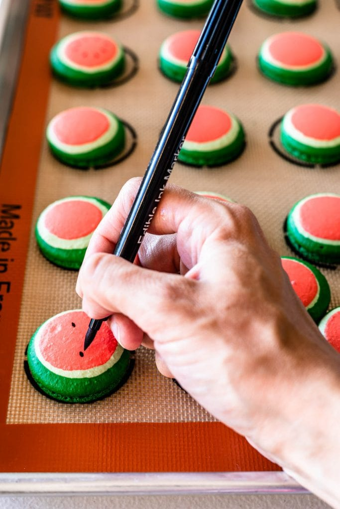 drawing on top of a macaron shell with a edible pen
