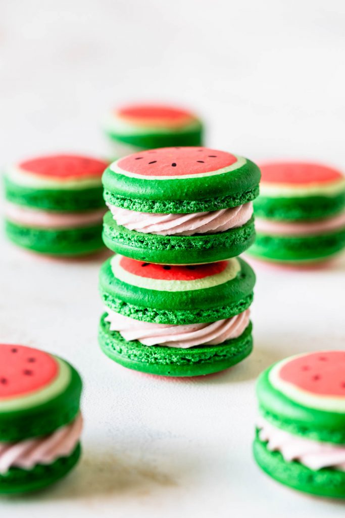macarons shaped like watermelon filled with buttercream stacked on top of each other