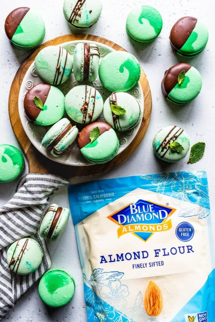 Mint Chocolate Macarons dipped in chocolate filled with ganache in a plate with a bag of Blue Diamond Almond flour