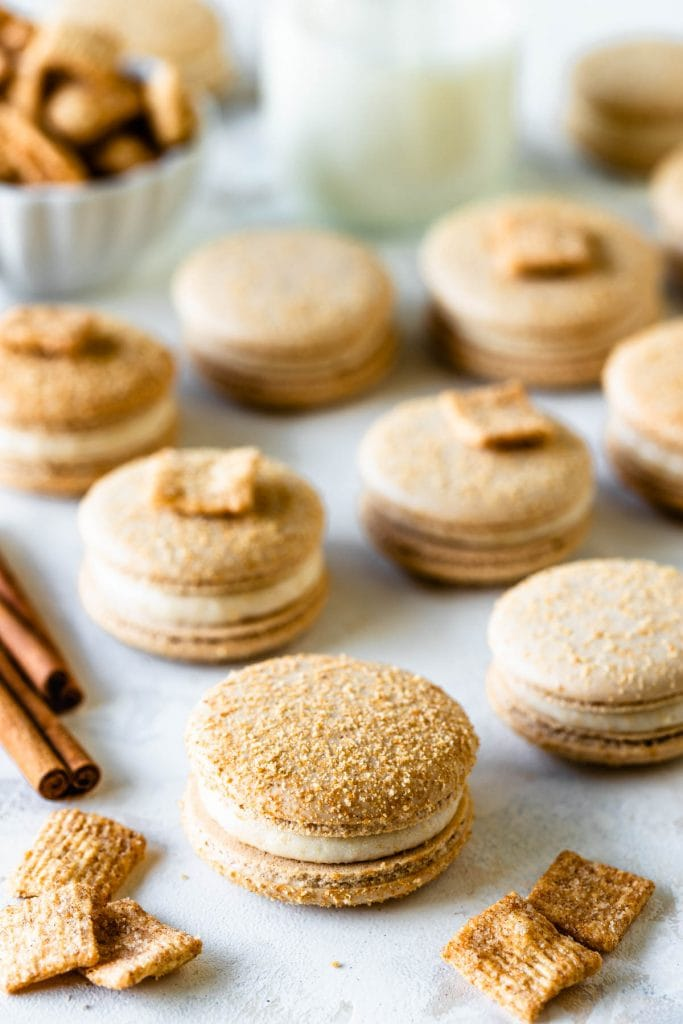Cereal macarons dusted with cinnamon toast crunch cereal powder, filled with cinnamon toast crunch buttercream