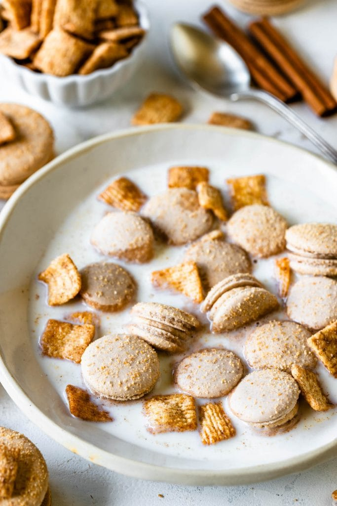 cereal macarons in a bowl with cinnamon toast crunch cereal and milk