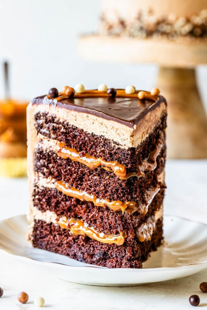 slice of chocolate cake filled with dulce de leche, topped with mocha buttercream and chocolate ganache, and crispearls