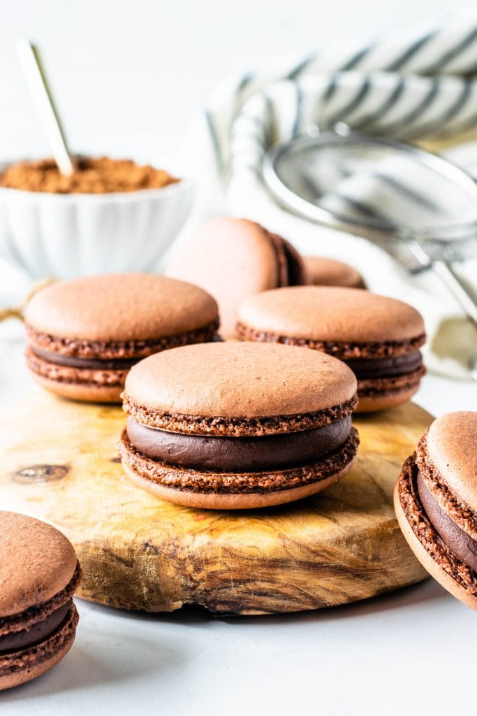 chocolate vegan macarons filled with chocolate ganache on top of a wooden board