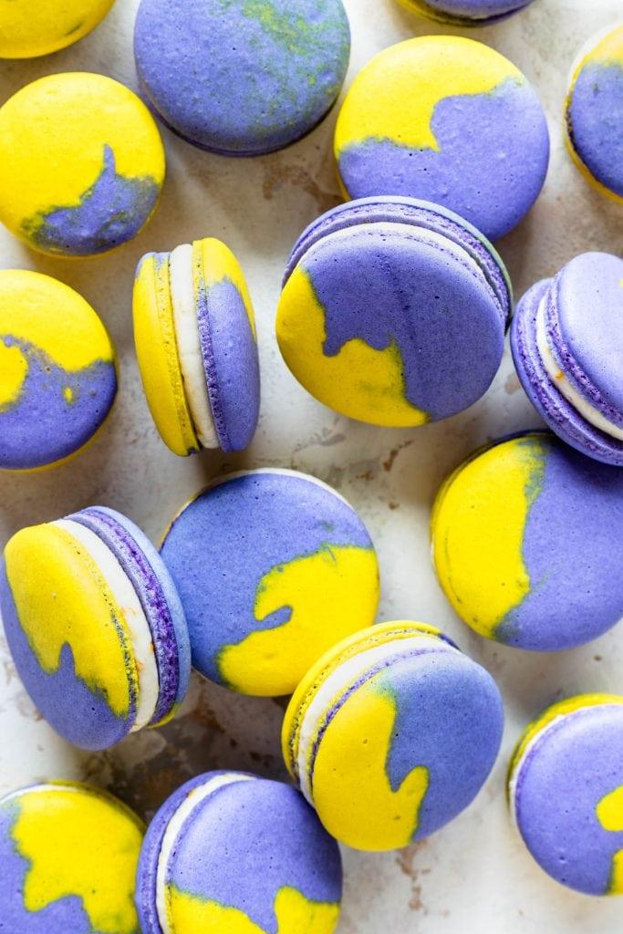 Vegan Lemon Blueberry Macarons purple and yellow shells filled with lemon buttercream, the macaron shells are purple and yellow