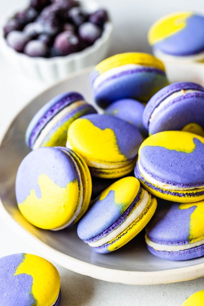 purple and yellow vegan macarons filled with buttercream in a plate