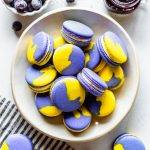 vegan macarons the shells are purple and yellow, they are filled with lemon buttercream and are in a white bowl with a container with blueberries and a container with jam around