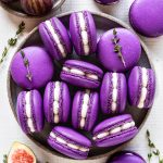 purple macarons filled with fig jam and buttercream seen from the top, with sprigs of thyme all around, and fresh figs on the top left corner and on the bottom left corner.