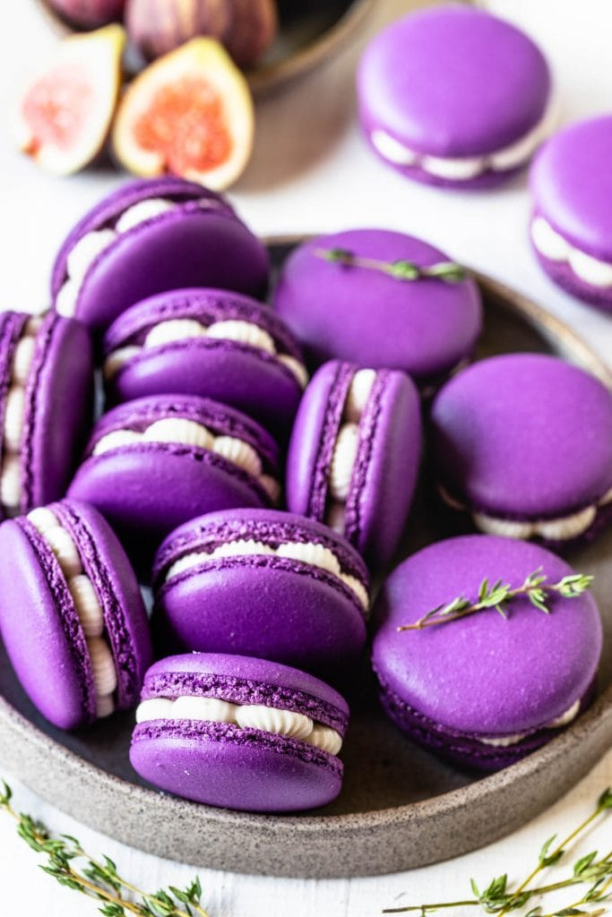 fig macarons on a plate filled with fig jam and buttercream, with thyme as a garnish on top, and figs on the picture as well, to decorate.