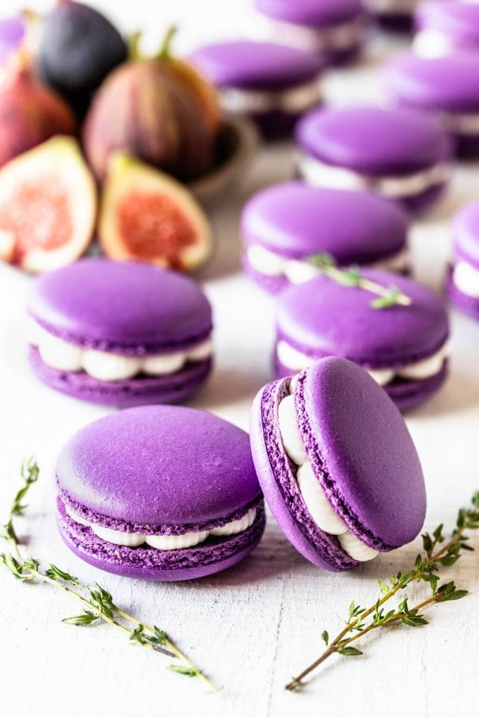 fig macarons filled with fig jam and buttercream, with thyme as a garnish on top, and figs on the picture as well, to decorate.