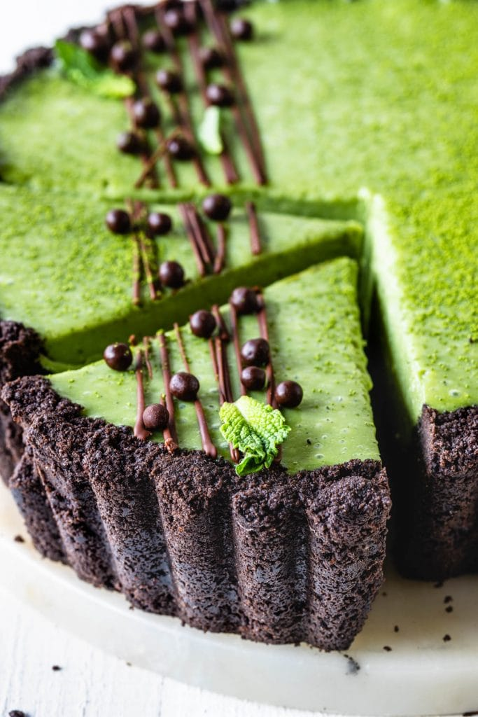 Matcha Pie with oreo crust and drizzled with chocolate and callebaut crispearls sliced