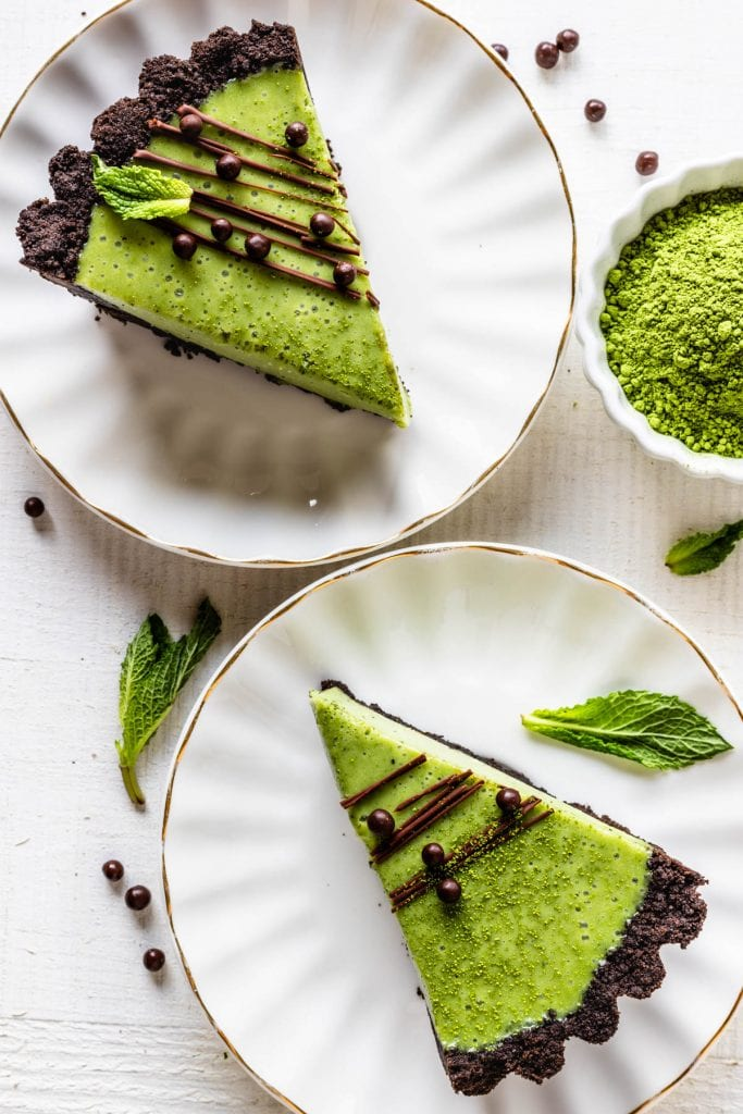 Matcha Pie with oreo crust and drizzled with chocolate and callebaut crispearls sliced with a bowl of matcha on the side, seen from the top