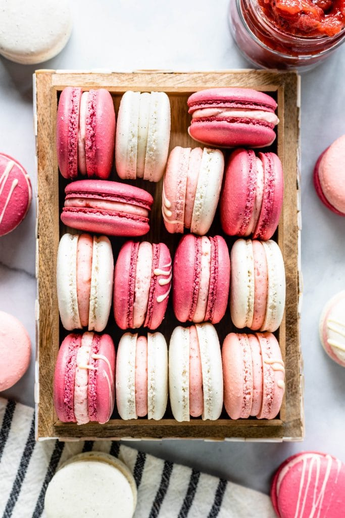 pink and white macarons with pink and white buttercream in a box, seen from the top with a jar of jam on the top.