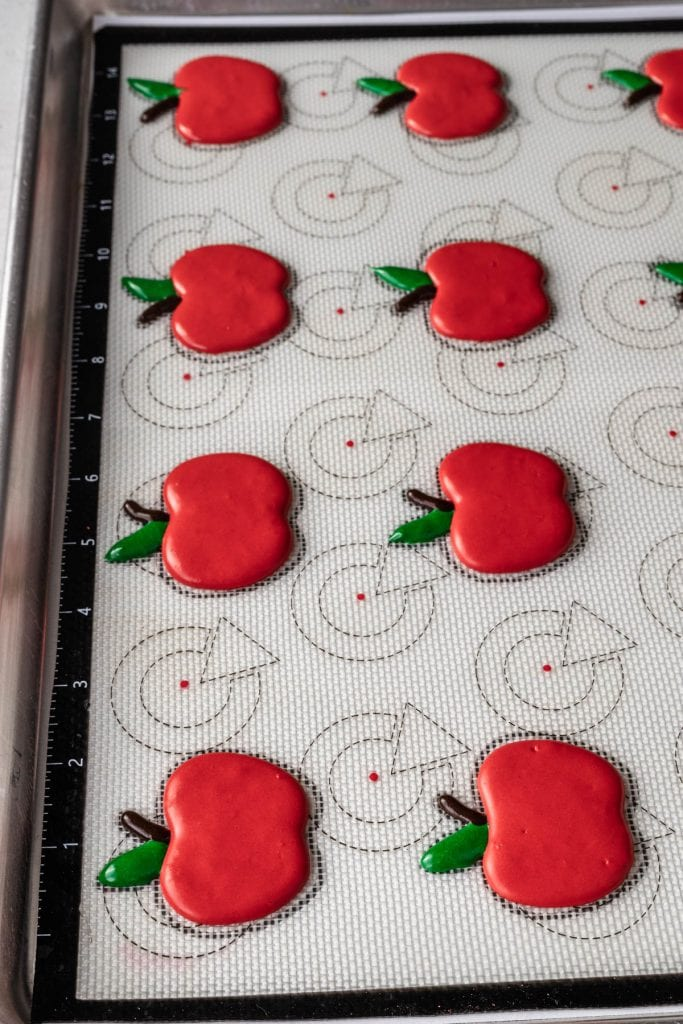 caramel apple macarons shaped like apples piped on a baking sheet.
