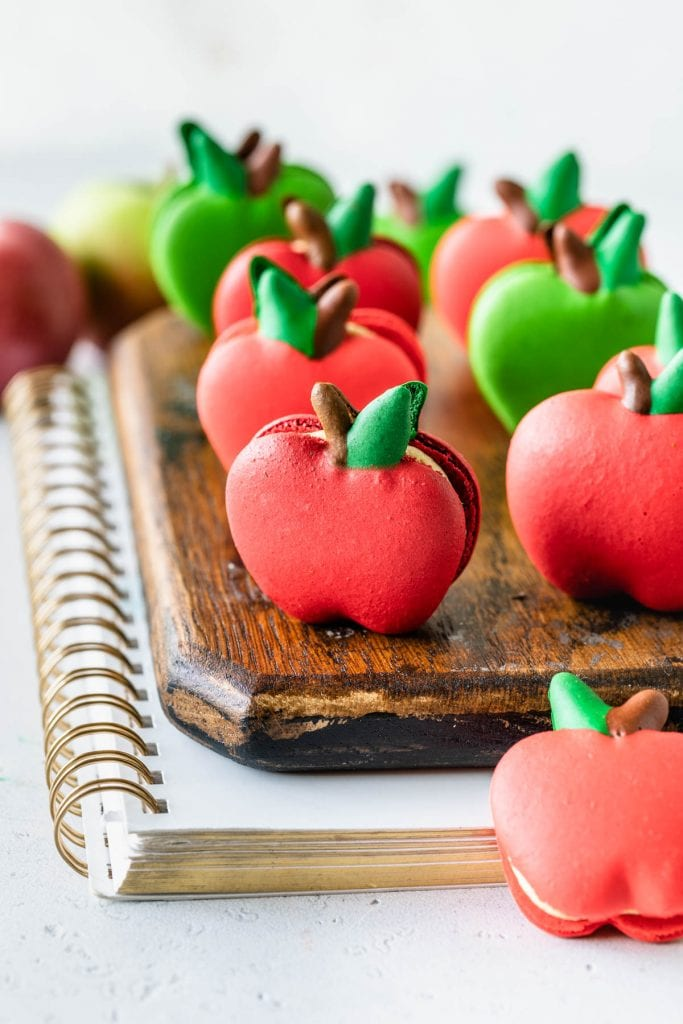 macarons shaped like apples on top of a wooden board and a notebook.