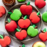macarons shaped like apples on a plate with caramel sauce on the side and an apple.